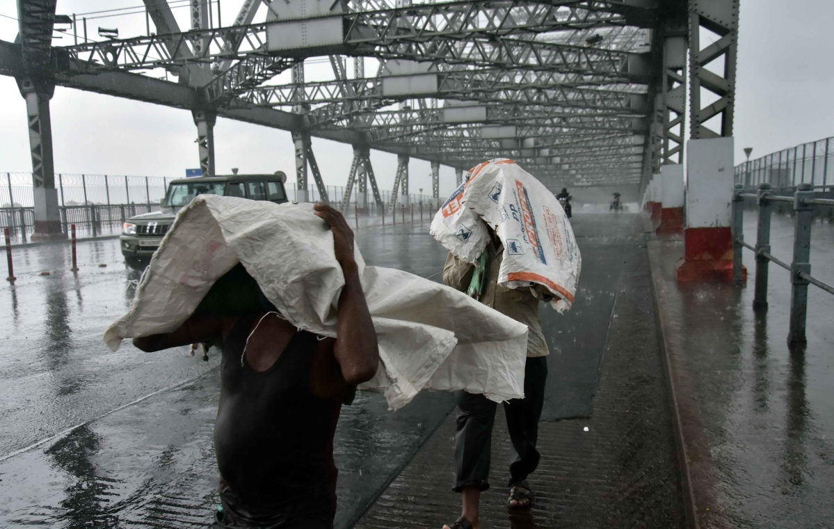 People cover themselves with plastic covers as they cross the Howrah Bridge during rain as a result of the prevailing conditions of Cyclone Amphan in Kolkata on Wednesday
