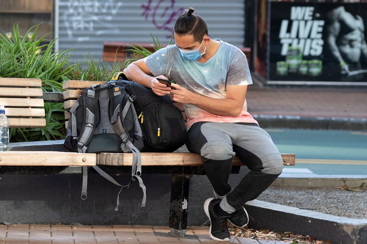 A man waits for his bus in Wellington.