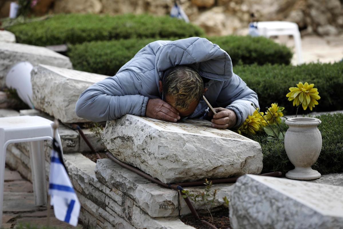 An Israeli man grieves over the grave of a loved one at the Mount Herzl military cemetery in Jerusalem.