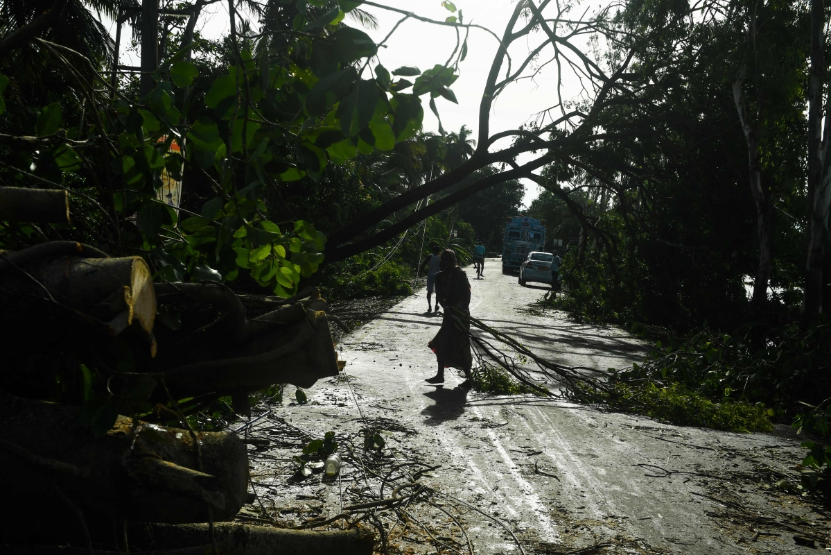 A woman walks past the damage left behind thanks to Cyclone Amphan