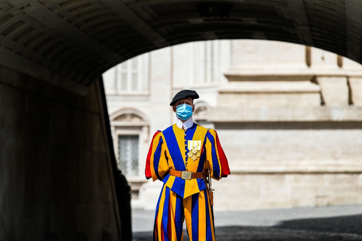 A Swiss Guard wearing a face mask stands guard by St. Peters Basilica in Vatican City.