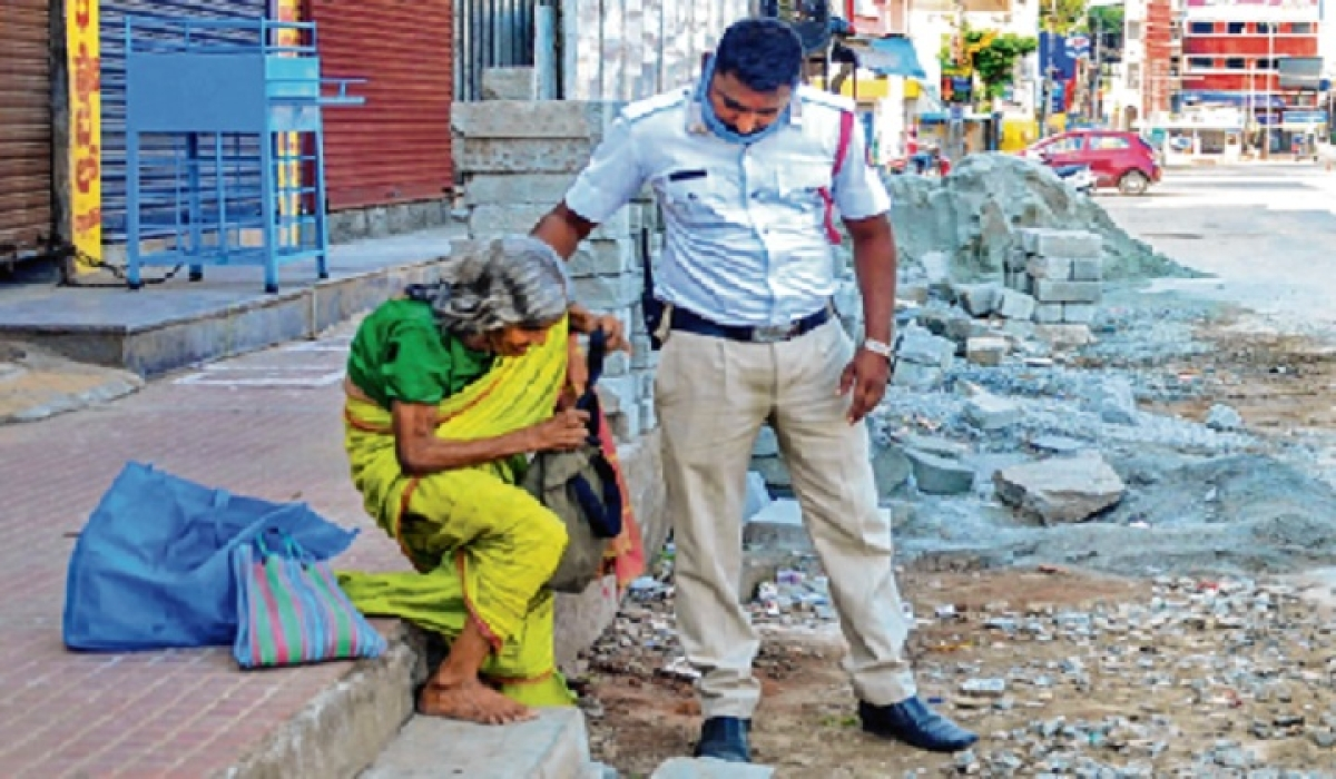 A cop offers help to an elderly woman in Chikmagalur, Karnataka, on Sunday.