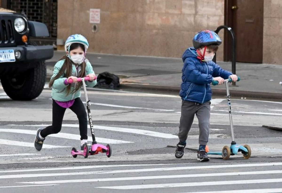 Children wearing face masks play on their scooters in New York City.