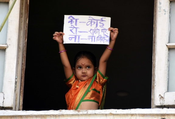 A little girl holds up a sign
