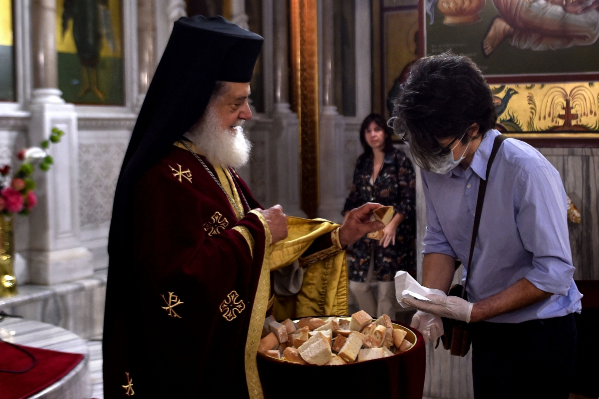 A priest gives the Holy Bread to a faithful wearing a protective face mask and gloves, in a church of Thessaloniki, Greece