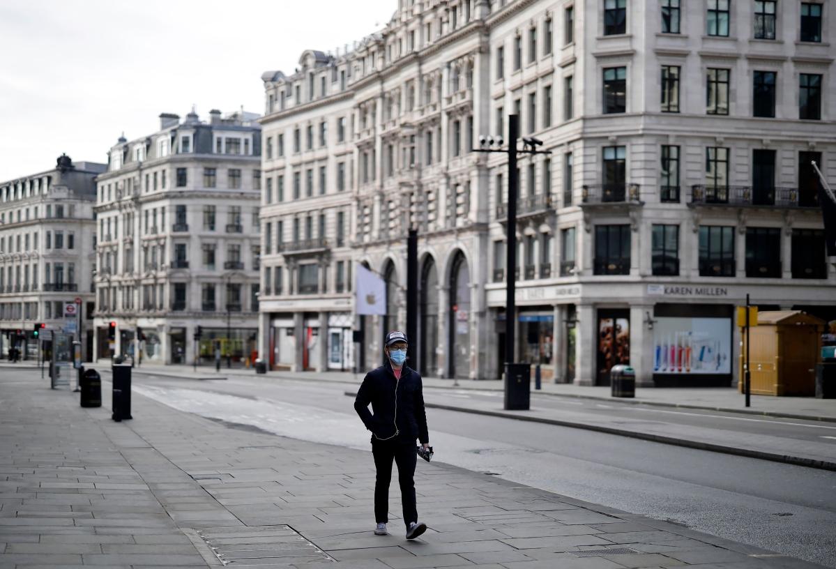 A pedestrian wearing a face mask, walks past closed-down shops on an empty Regent Street in London.