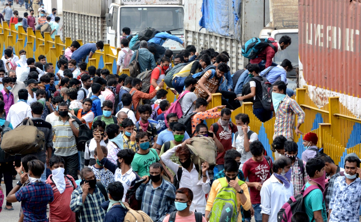 Long way home: Migrants queue for train tickets at Mumbai