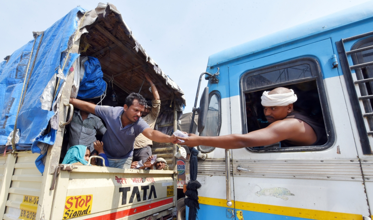 Water packets being passed as migrants travel in trucks to reach their hometowns at the Lucknow-Kanpur national highway.