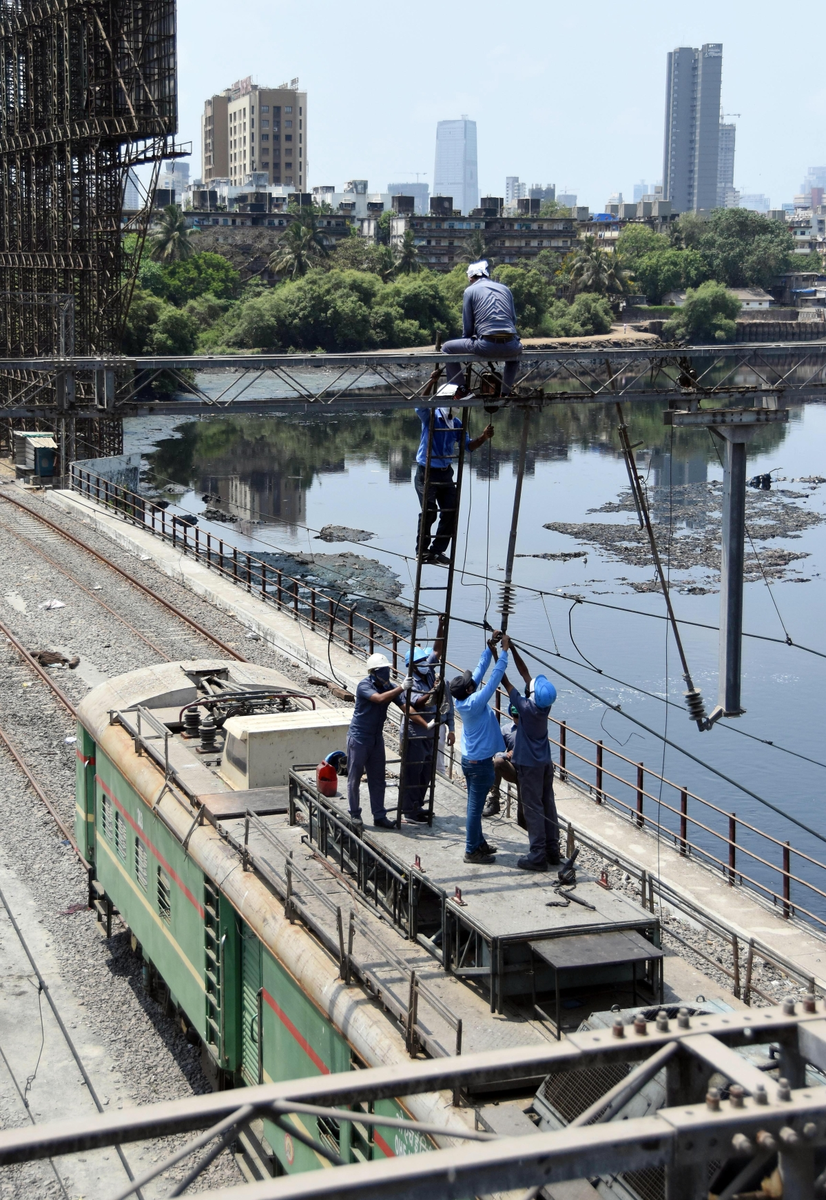 Labourers do the maintenance work on Western Railway lines near Bandra station during the nationwide lockdown, in Mumbai