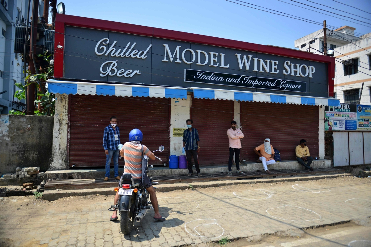 People stand as they wait to buy alcohol at a liquor shop after the government eased a nationwide lockdown as a preventive measure against the COVID-19 coronavirus, in Allahabad