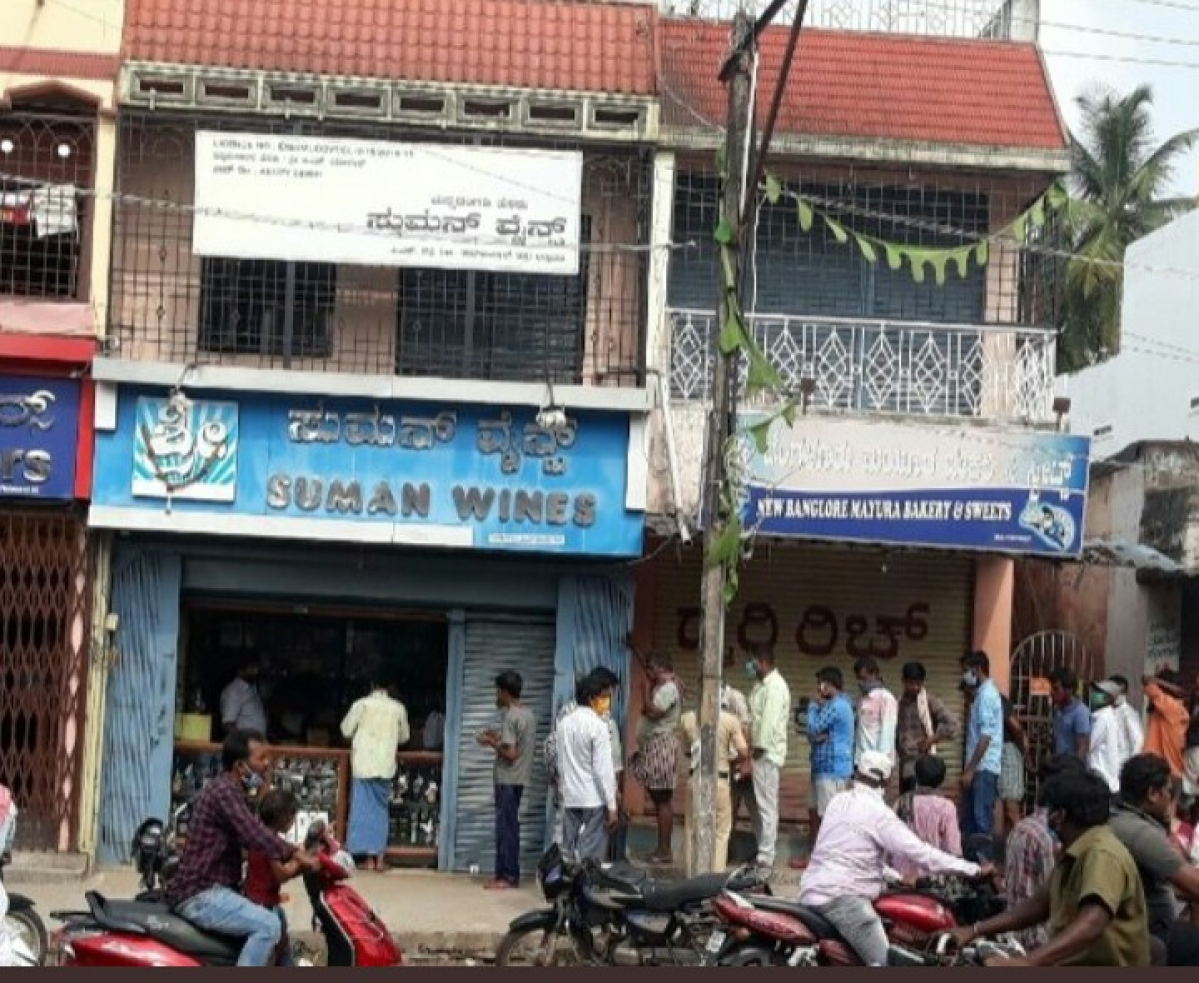 People wait in queue to buy liquor.