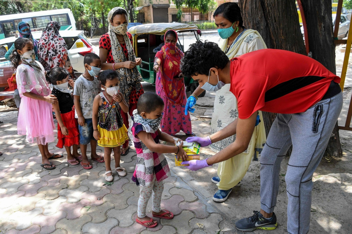 Slum children receive chocolate cookies and soap from a volunteer (R) of an NGO in New Delhi on Saturday/ File