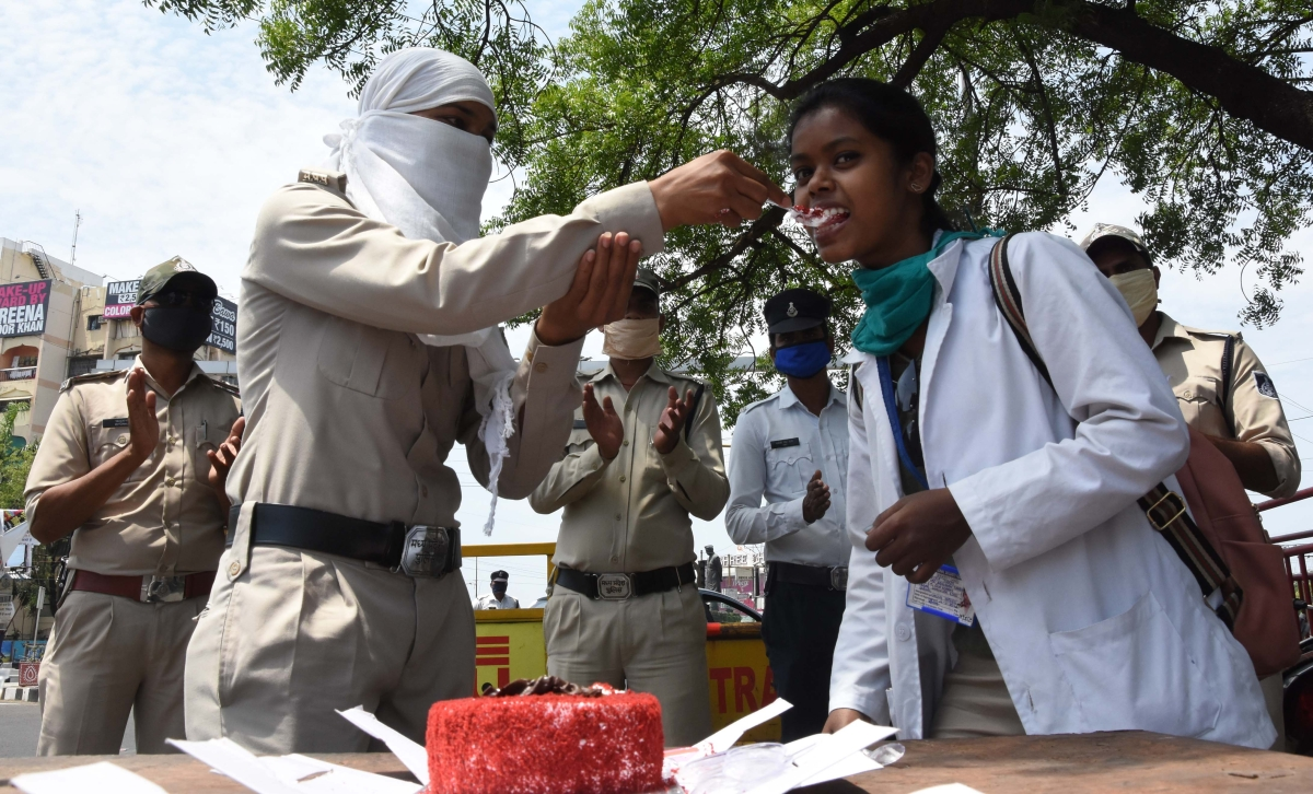Police personnel offers a piece of cake to nursing students as they celebrate International Nurses Day during a Povernment-imposed nationwide lockdown in Bhopal on Tuesday.