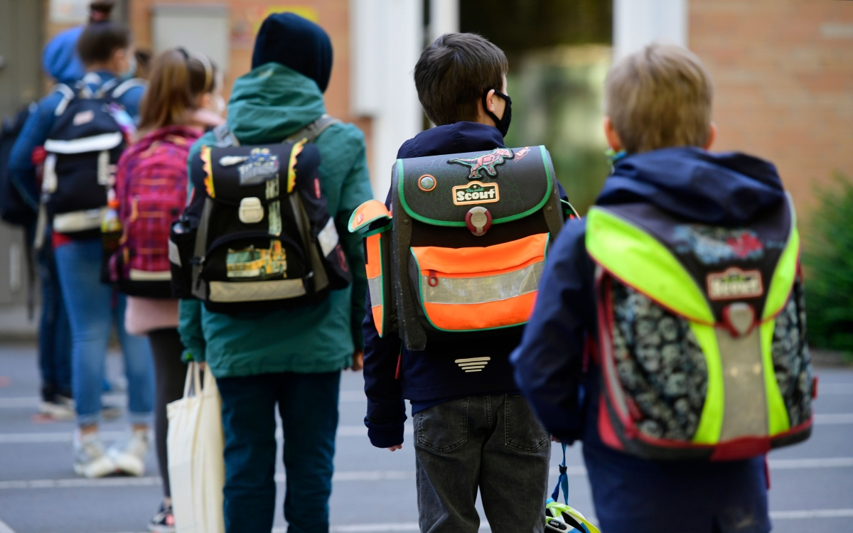 Children respect social distancing rules as they line up to enter the Petri primary school in Dortmund, western Germany