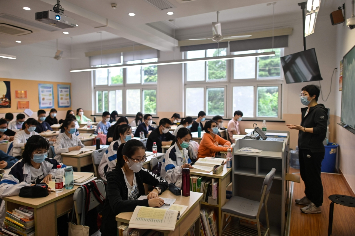 Students wearing face masks are seen in their classroom during a government organised media tour at Shanghai High School.