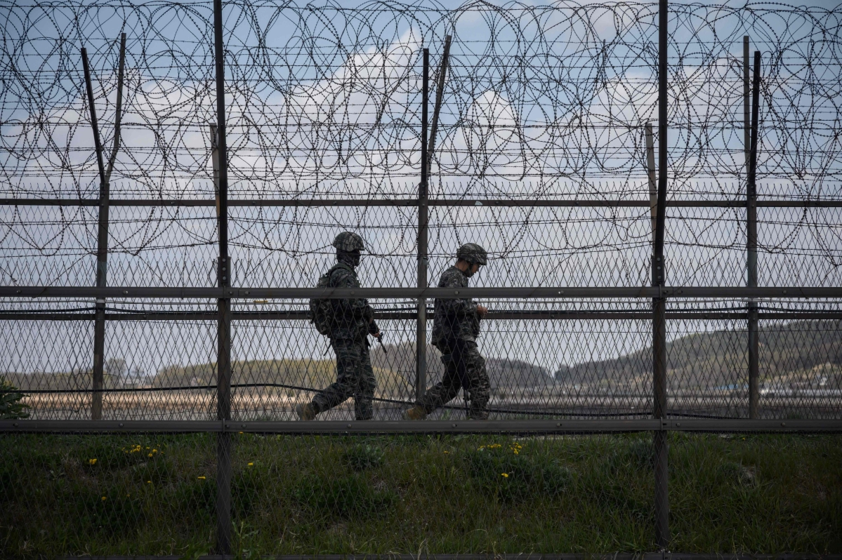 South Korean soldiers patrolling along a barbed wire fence Demilitarized Zone (DMZ) separating North and South Korea, on the South Korean island of Ganghwa.