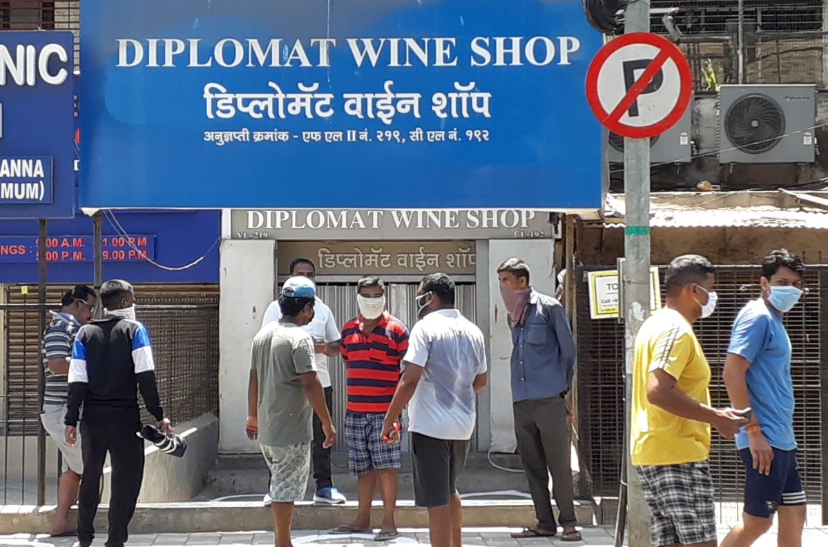 Customers stand outside a wine shop in Andheri