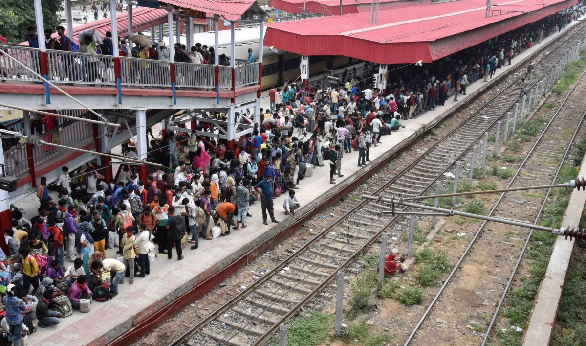 Migrants, not adhering to social distancing norms, wait to board a train at Danapur railway station, during the nationwide lockdown, in Patna on Saturday.