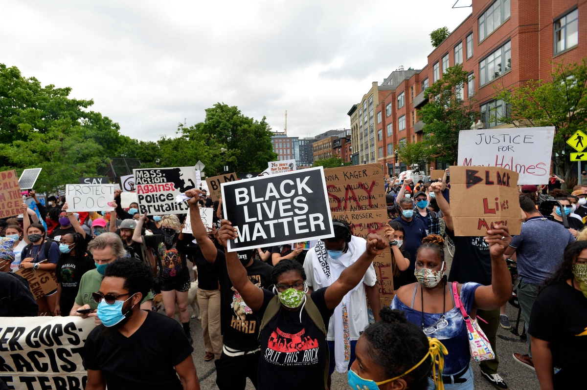 Protesters hold signs as they gather to protest police brutality and racism in the US, with the recent deaths of George Floyd, Ahmaud Arbery, Breonna Taylor, in Boston, Massachusetts.