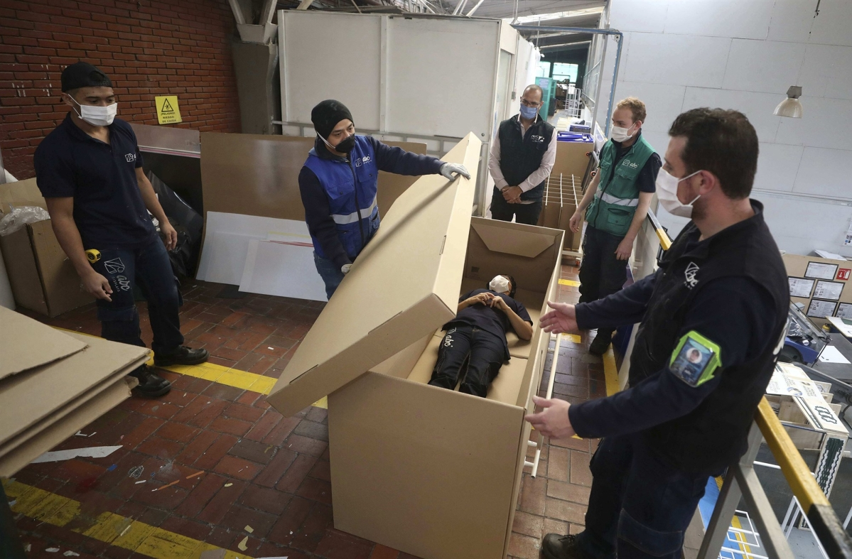 Rodolfo Gomez and his employees demonstrate how their design of a cardboard box can serve as both a hospital bed and a coffin.