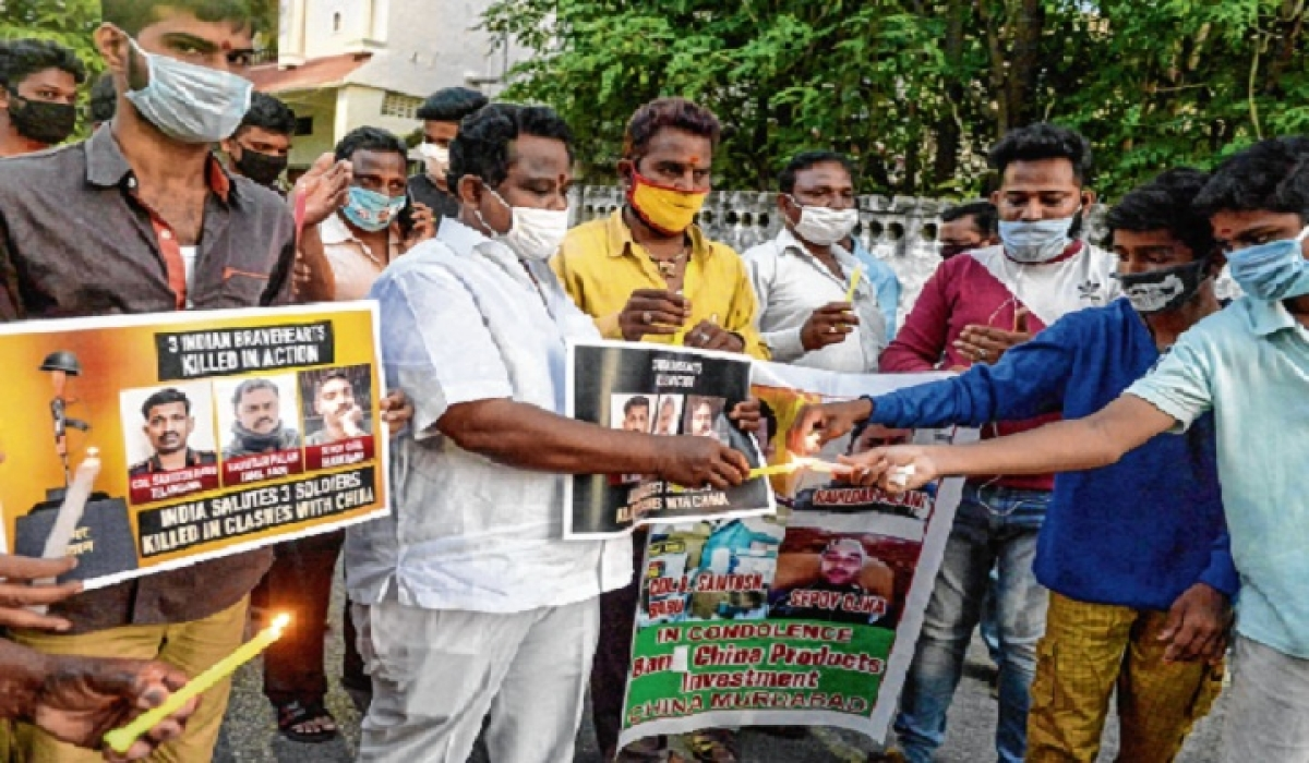 Youth organisation members hold posters and light candles to pay tribute to the soldiers, in Hyderabad.