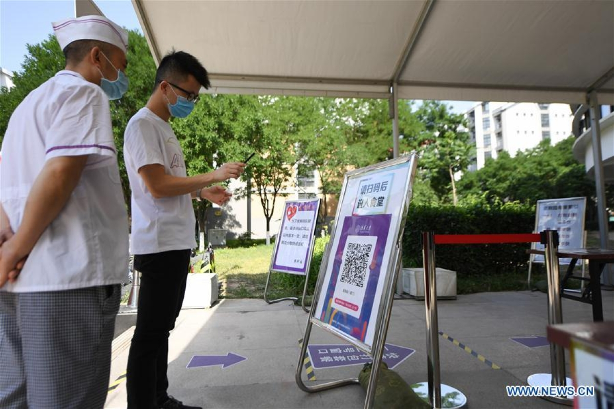 A student scans a QR code to register his health information in front of a canteen in Tsinghua University in Beijing, capital of China, June 6, 2020.