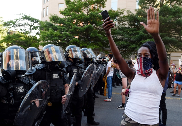 A protester holds up his hands in front of a row of police officers during a demonstration against the death of George Floyd at a park near the White House on June 1, 2020 in Washington, DC