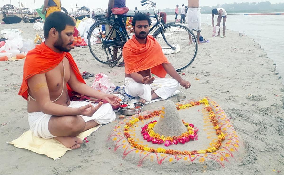 Devotees offering special prayers after Lunar eclipse near Sangam river, in Prayagraj on Saturday.