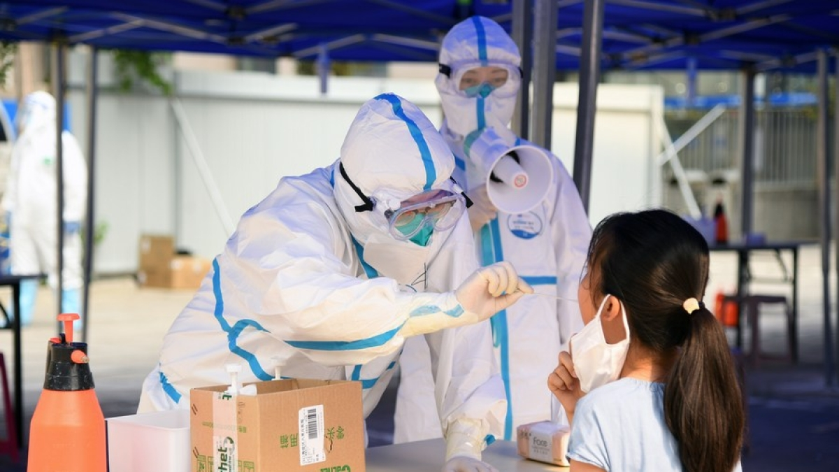 A medical worker collects a throat swab from a local resident at a nucleic acid testing site at a community in Balizhuang Street of Haidian District, Beijing, capital of China, June 23, 2020.
