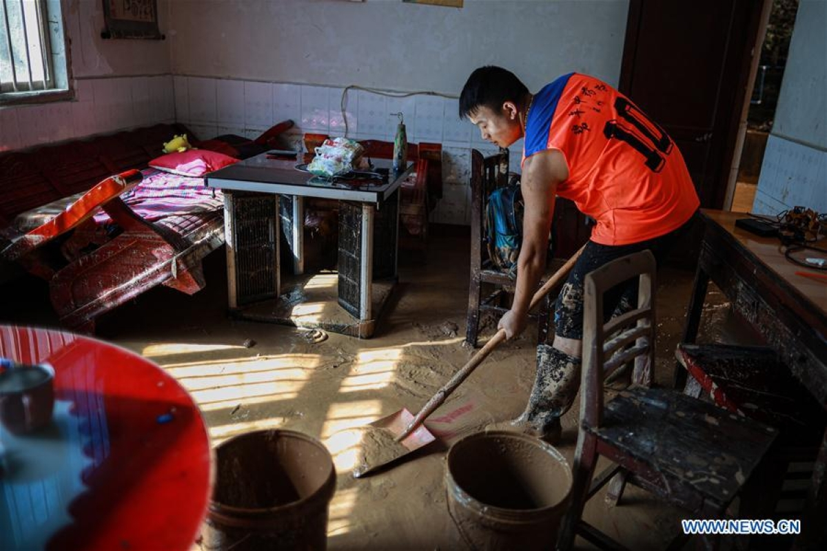 A resident cleans silt at his home in Bifeng Town of Zheng'an County in Zunyi, southwest China's Guizhou Province, June 13, 2020. Rain-triggered floods have affected more than 700,000 people in southwest China's Guizhou Province, with 29,500 individuals temporarily evacuated, authorities said Saturday.