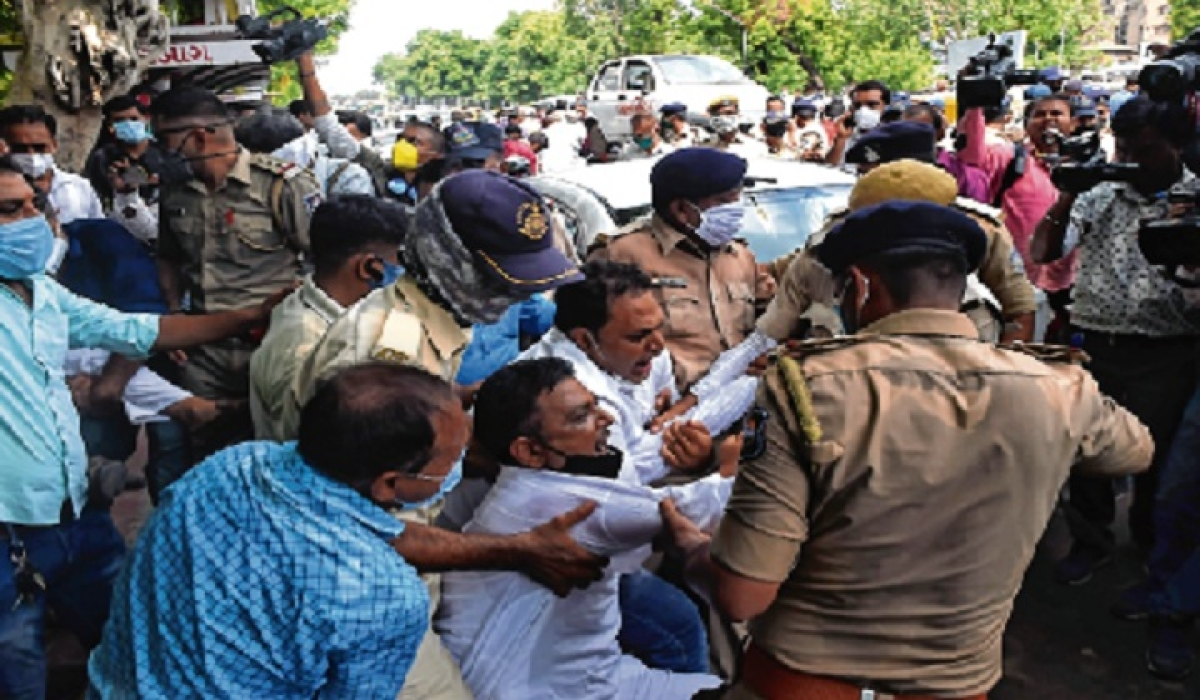 A Gujarat Congress supporter shouts anti-government slogans as cops detain him in Ahmedabad on Monday.