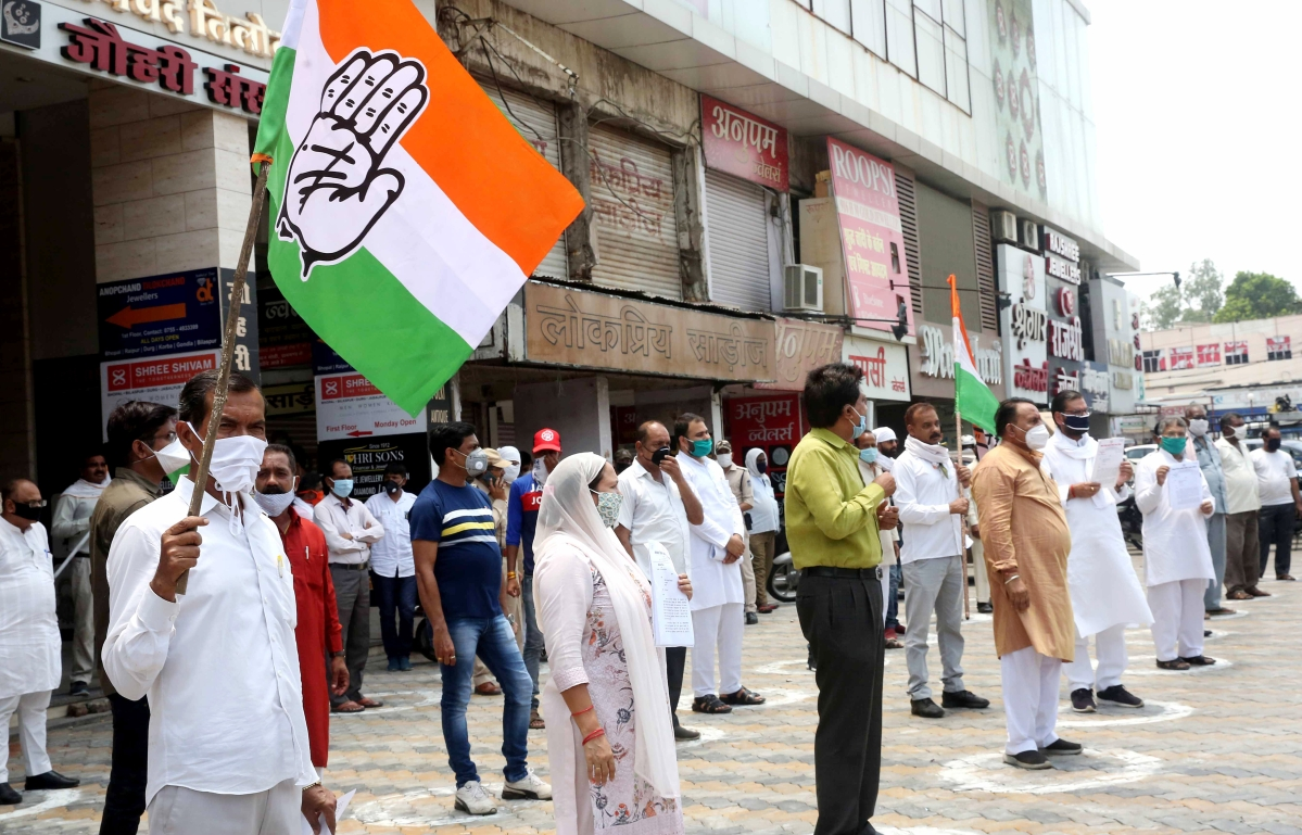 Congress party activists maintaining social distancing demonstrate against Chief Minister Shivraj Singh Chouhan blaming to dislodge Kamal Nath led ruling Congress Government in the State on the decision of central leadership after his audio clip went viral, during ongoing COVID-19 lockdown in Bhopal on Friday.