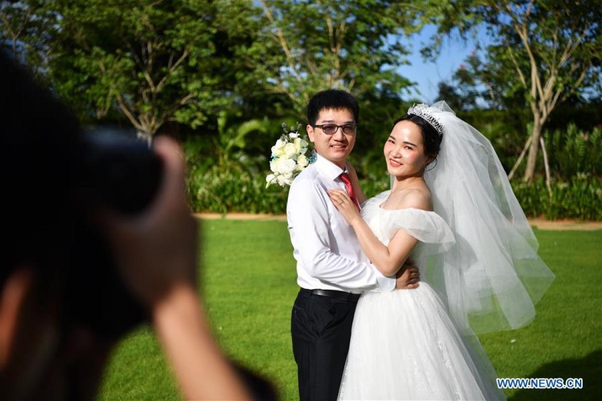 Ke Quan, a nurse from Renmin Hospital of Wuhan University, poses for a wedding photo with Yu Chen (R) at a resort in Sanya City, south China's Hainan Province, June 6, 2020. A group wedding ceremony was held here Saturday for newly-married couples from 15 provinces nationwide who once worked to fight against the COVID-19 outbreak.
