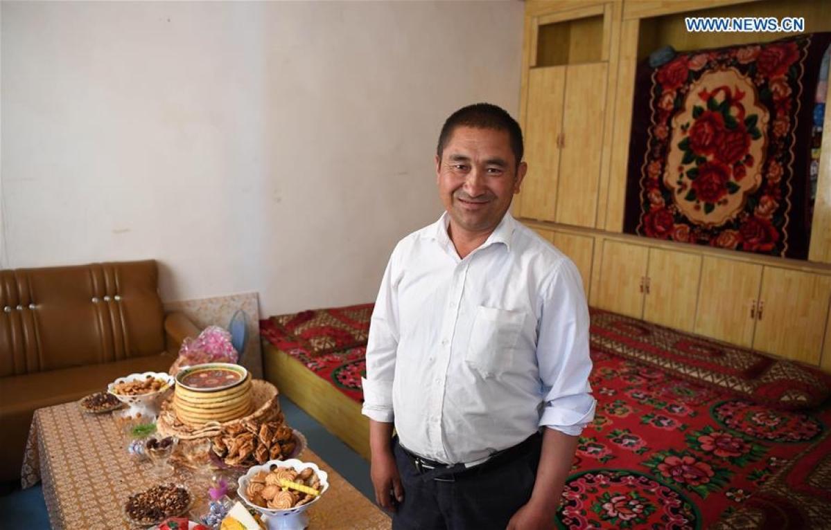 Villager Ruzamamet Matkerim smiles in his house in Inilik Village of Hotan Prefecture, northwest China's Xinjiang Uygur Autonomous Region, May 25, 2020.