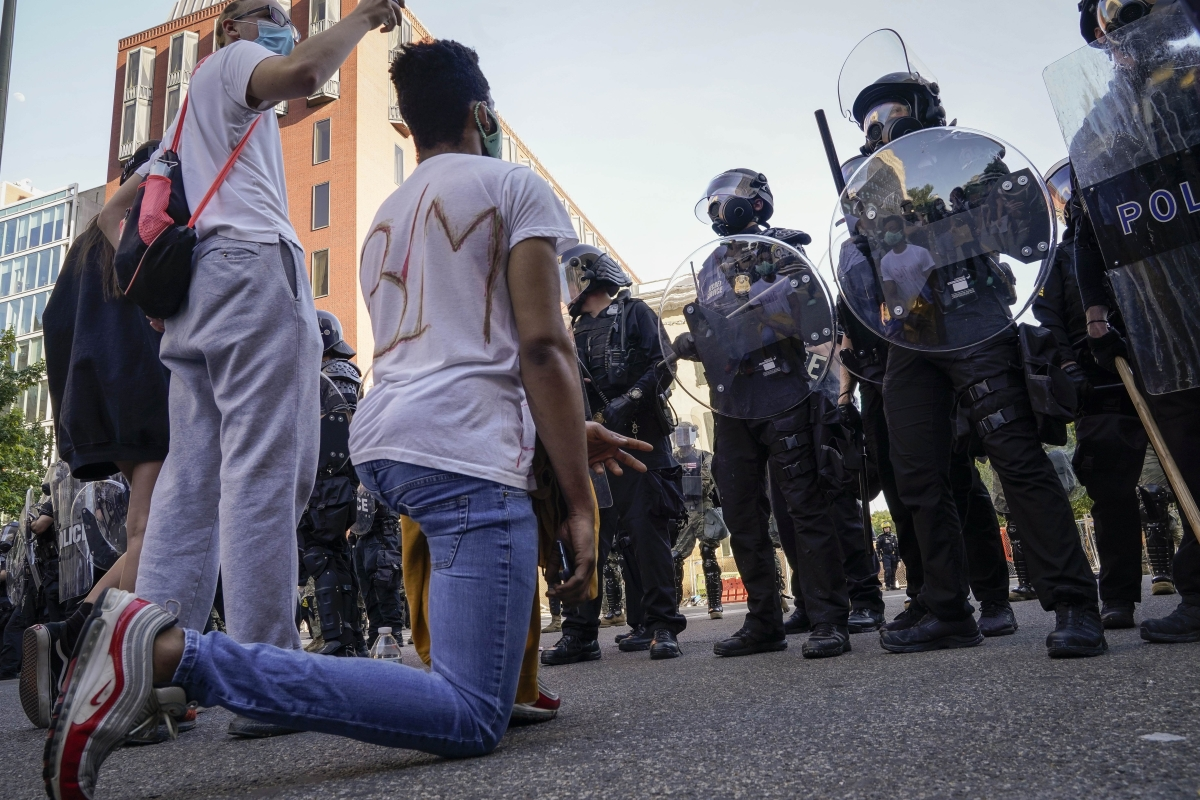 A protestor kneels before a cop during the nationwide protests in the United States