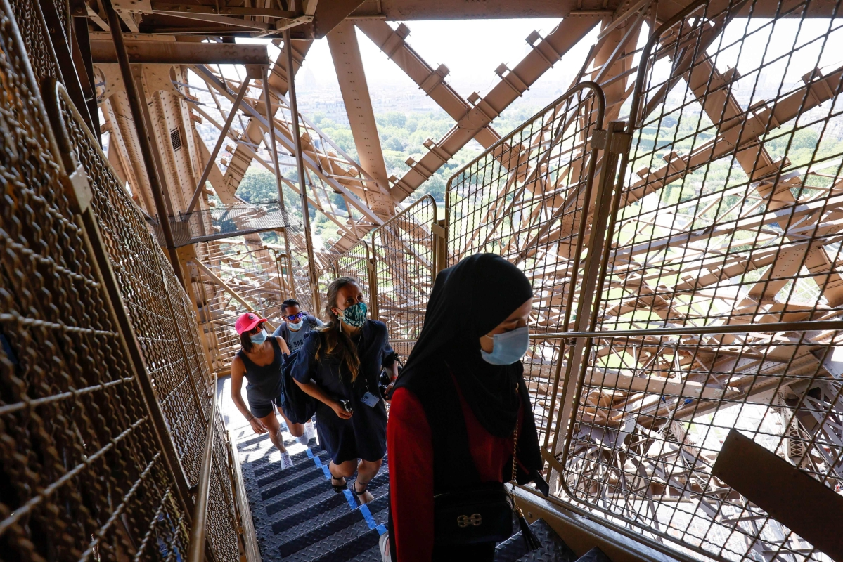 Visitors wearing protective face masks walk up the stairs as they visit the Eiffel Tower during its partial reopening