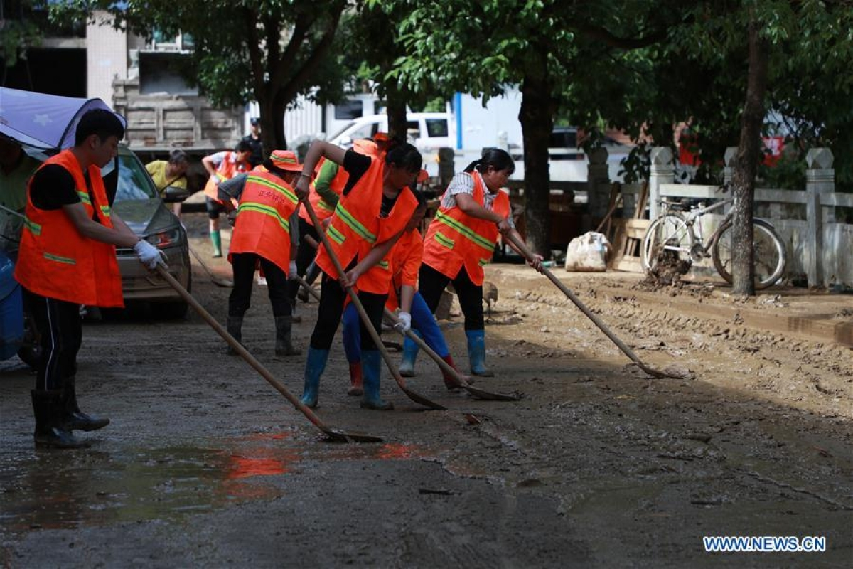 Rescuers clean silt on the street in Bifeng Town of Zheng'an County in Zunyi, southwest China's Guizhou Province, June 13, 2020. Rain-triggered floods have affected more than 700,000 people in southwest China's Guizhou Province, with 29,500 individuals temporarily evacuated, authorities said Saturday.