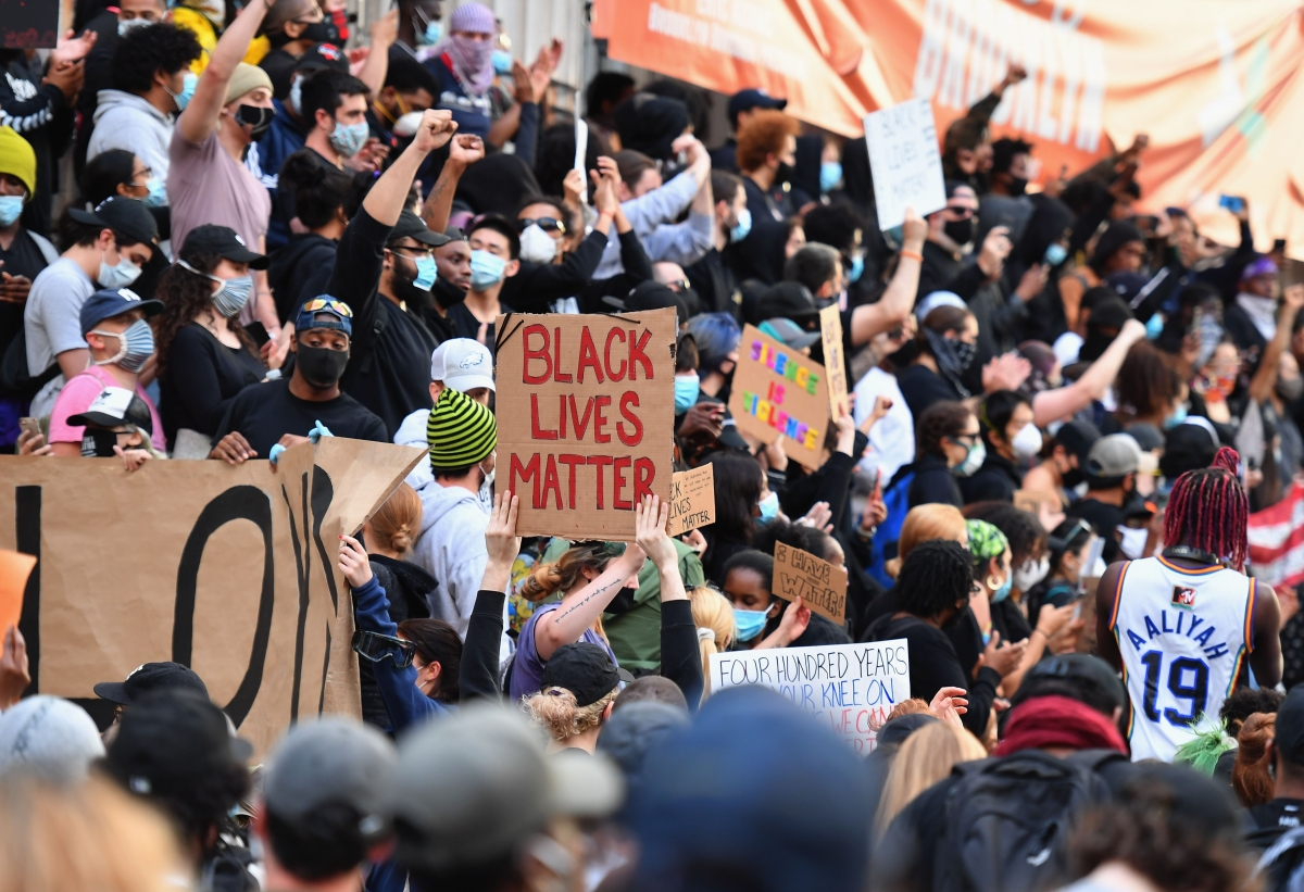 """Protestors hold up placards and raise their arms during a """"Black Lives Matter"""" demonstration over the death of George Floyd by a Minneapolis police officer, at Brooklyn Borough Hall on June 1, 2020 in New York."""