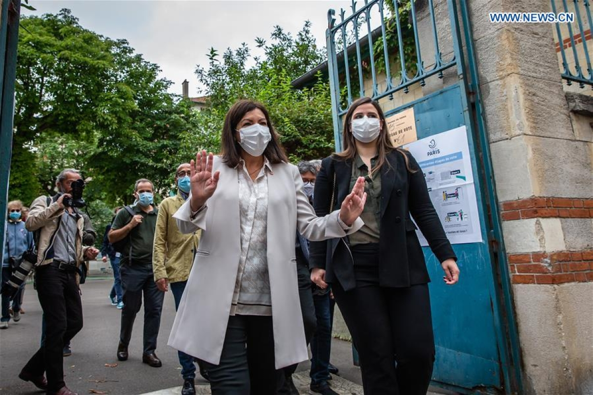 The incumbent Mayor of Paris Anne Hidalgo (L, front) leaves a polling station of the 15th district during the second round of municipal elections in Paris, France, June 28, 2020.