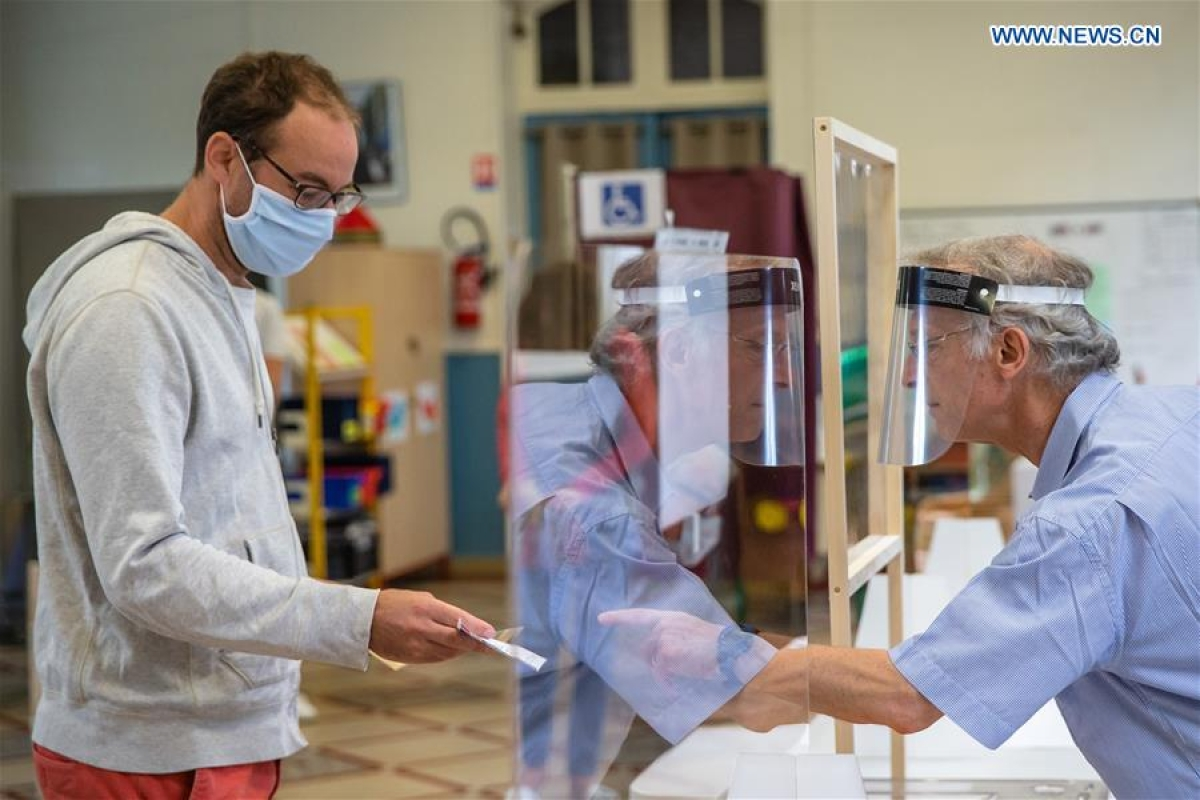A man wearing a protective mask prepares to vote at a polling station during the second round of municipal elections in Paris, France, June 28, 2020