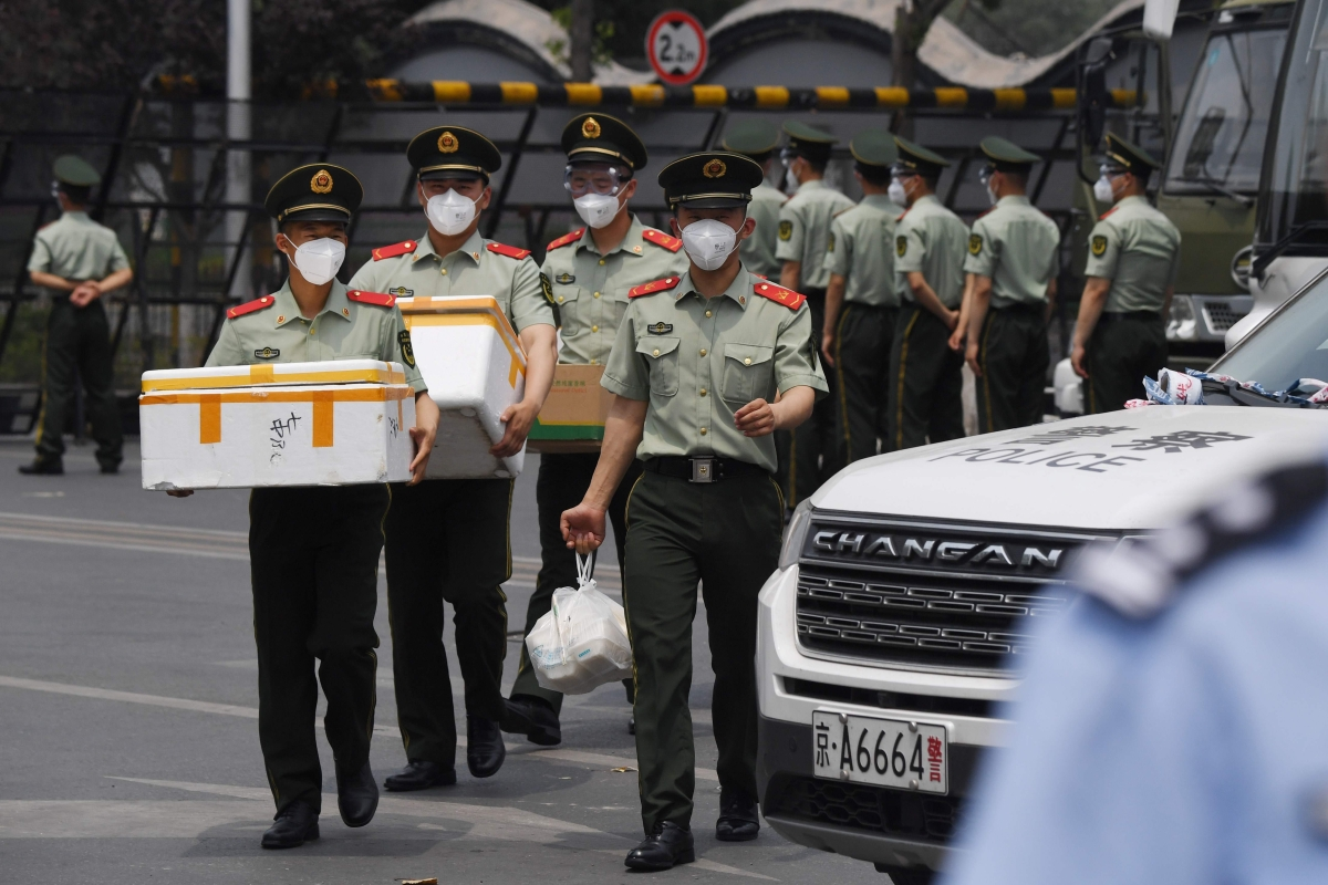 Paramilitary police officers wear face masks as they prepare food supplies at the entrance to the closed Xinfadi market in Beijing.
