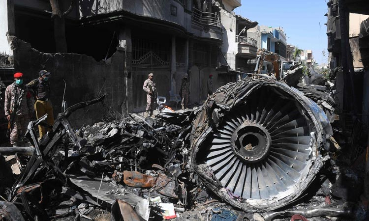 Security personnel stand beside the wreckage of the crashed PIA plane in a residential area in Karachi.