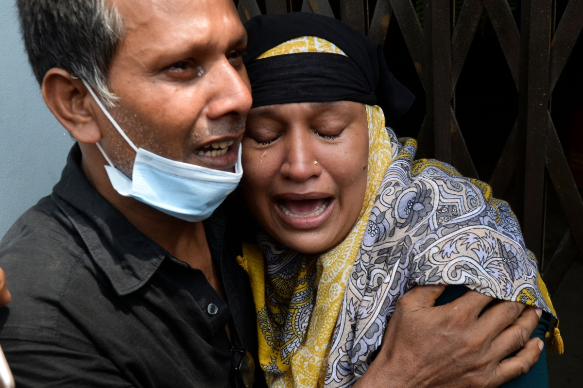 Relatives of a victim of sunken ferry mourn as rescue workers unload bodies in Dhaka.