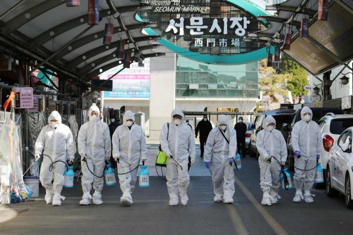 Market workers wearing protective gear spray disinfectant at a market in the southeastern city of Daegu, South Korea