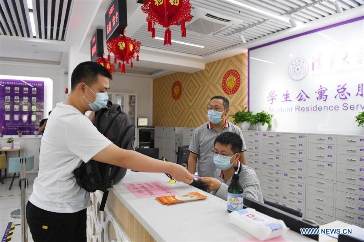 A student (1st, L) goes through procedures to move to his dormitory at Tsinghua University in Beijing, capital of China, June 6, 2020.