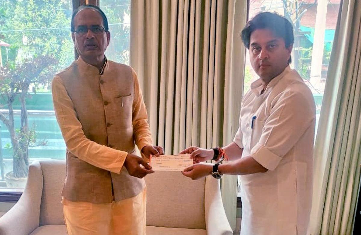 BJP leader Jyotiraditya Scindia meets Madhya Pradesh Chief Minister Shivraj Singh Chouhan and handover a relief cheque for COVID19 fund, New Delhi on Monday.