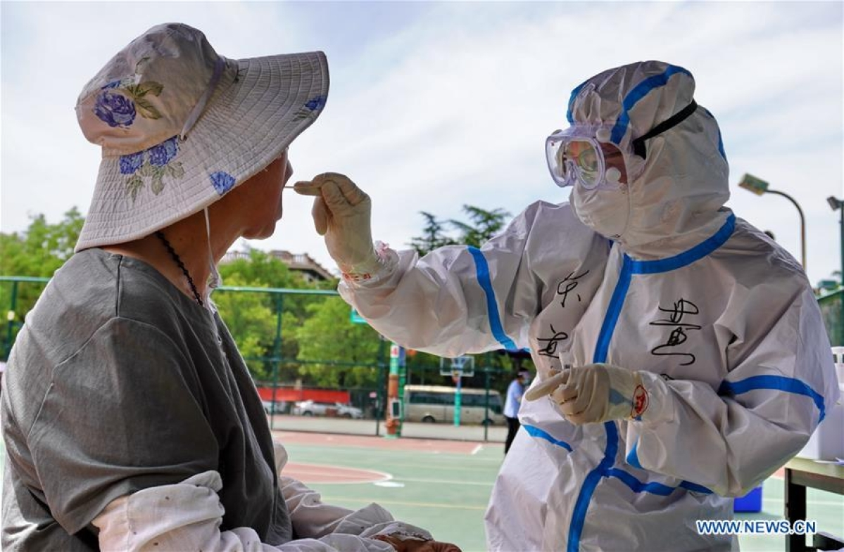 A medical worker collects throat swab of a resident at a sampling site in Fengtai District of Beijing, capital of China, June 15, 2020. Beijing on Sunday conducted nucleic acid tests on 76,499 people, with 59 testing positive for COVID-19, according to a press conference held Monday. As of 6 a.m. Monday, 193 sampling sites had been set up across Beijing to facilitate nucleic acid testings, said Gao Xiaojun, spokesperson for the municipal health commission.