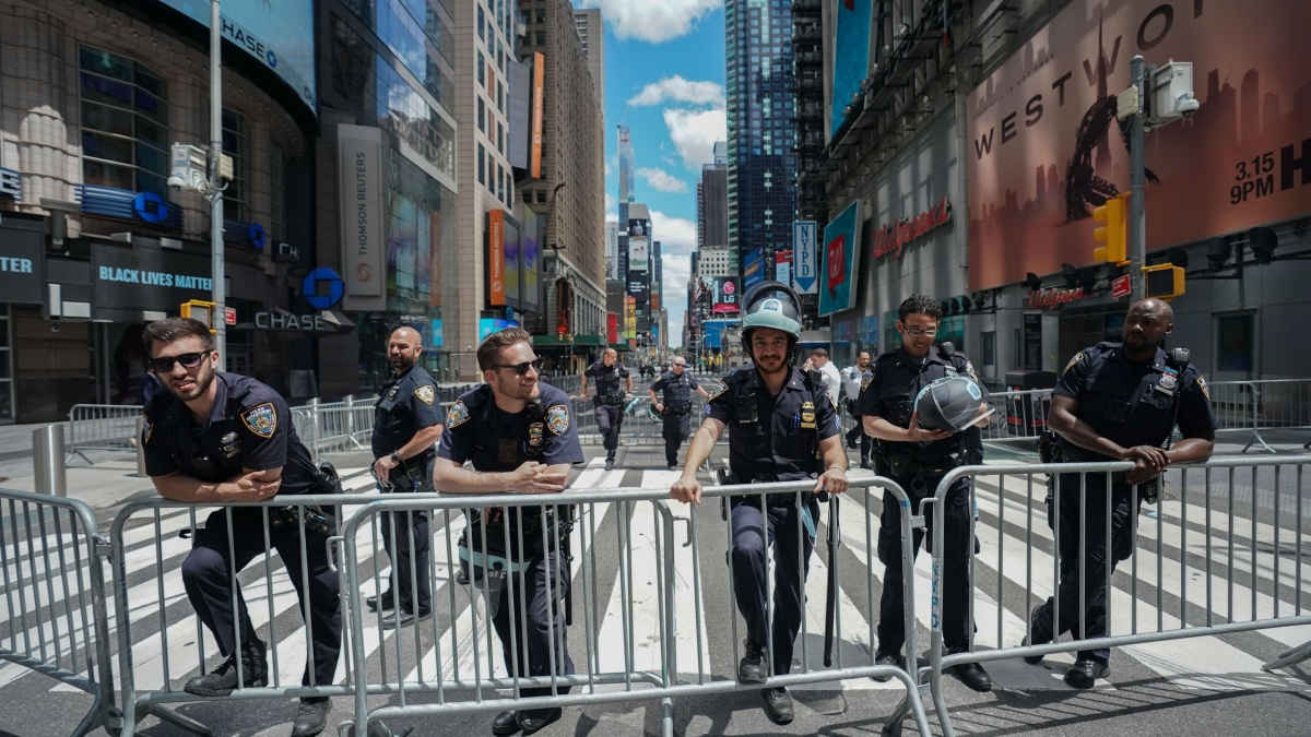 Members of the New York City Police Department look on as Black Lives Matter protesters demonstrate in Times Square.