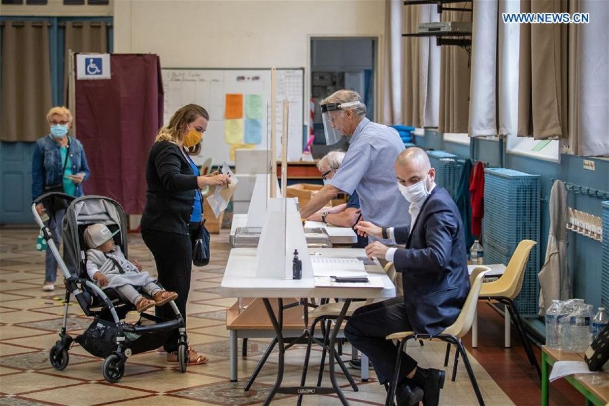 People wearing protective masks prepare to vote at a polling station during the second round of municipal elections in Paris, France, June 28, 2020.