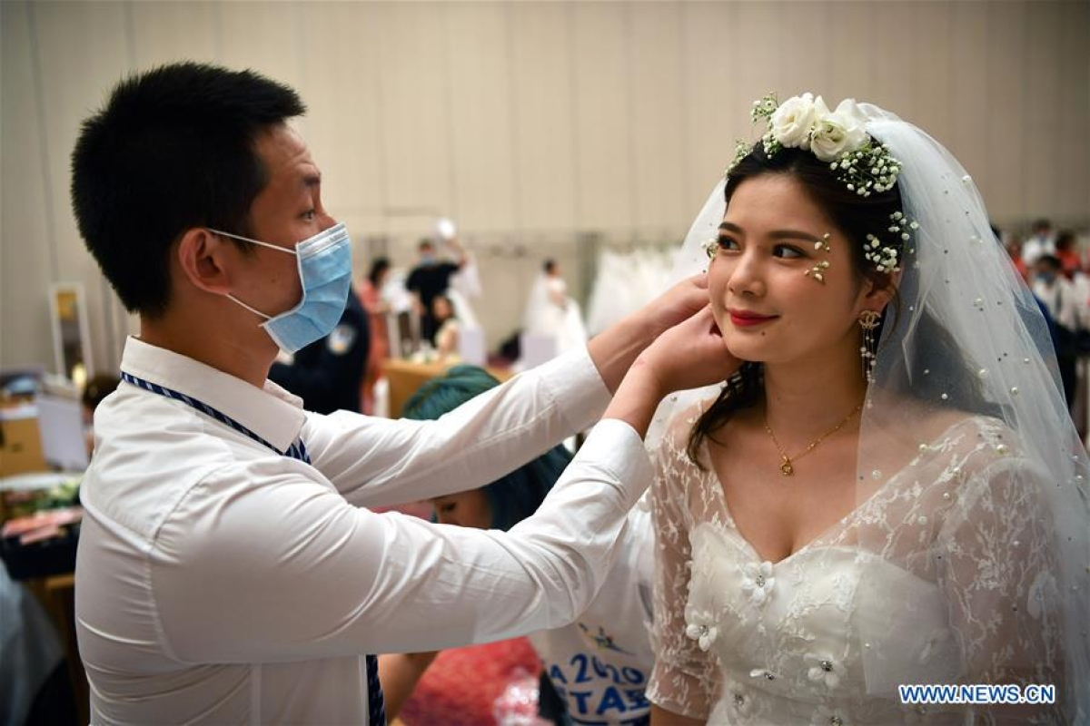 Chen Jianming, a senior nurse from Hunan Provincial People's Hospital who once was dispatched to Huanggang City in Hubei Province for the fight against COVID-19, helps his wife Tang Chan, who is also a medical worker, wear earrings at a resort in Sanya City, south China's Hainan Province, June 6, 2020. A group wedding ceremony was held here Saturday for newly-married couples from 15 provinces nationwide who once worked to fight against the COVID-19 outbreak.